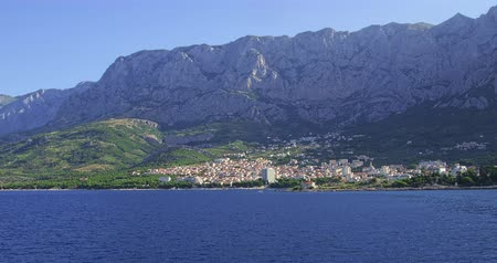 traverse : Beautiful city of Makarska shot from sea side, residential area in summer morning.