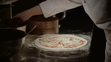 prepare food : Cheef placing ingredients for the pizza on the metal surface of the kitchen. Stock Footage