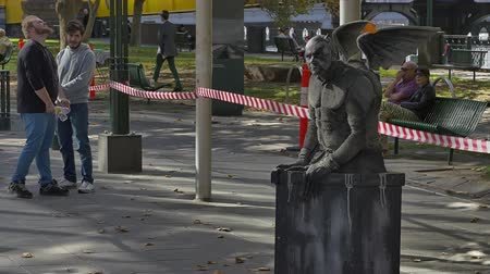 гот : MELBOURNE AUSTRALIA  MARCH 21 2015: Gargoyle interactive clown show with a character that just happens to be a statue performing at Southbank promenade.