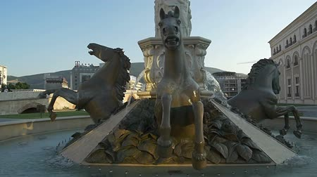 szökőkút : SKOPJE, MACEDONIA - JULY 17, 2015: View of the Horses fountain in Macedonia Square in new part of the capital city in twilight.