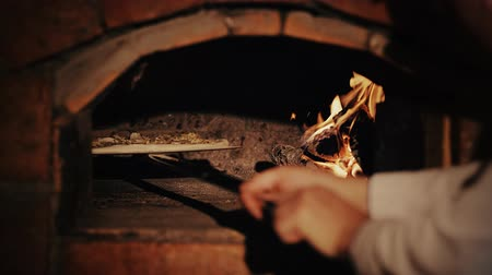 forno : Cheef puts pizza into the wood burning oven with the pizza shovel.