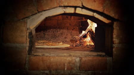 wood : Pizza baking in a wood burning oven. View of the opening. Stock Footage
