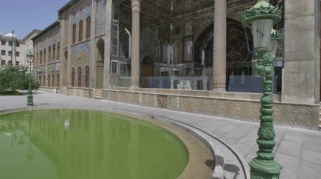 reconstructed : TEHRAN, IRAN - MAY 1, 2015: Golestan Palace exterior with green pool, panning from pool to the Marble throne of the former royal Qajar complex in capital city. Stock Footage
