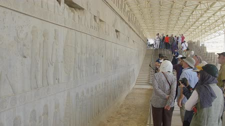 archeologický : PERSEPOLIS, IRAN - MAY 3, 2015: Tourist taking photo of the relief on the wall in old city ruins, a capital of the Achaemenid Empire 550 - 330 BC.