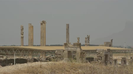 persie : PERSEPOLIS, IRAN - MAY 3, 2015: Visitors walking by the ancient pillars of the old city stand tall through time.