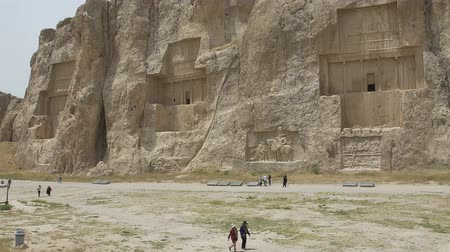archeologický : NAQSH-E RUSTAM, IRAN - MAY 3, 2015: The group of tourists with the tour guide in front of the historical monuments of ancient necropolis near ruins of old city Persepolis. Dostupné videozáznamy
