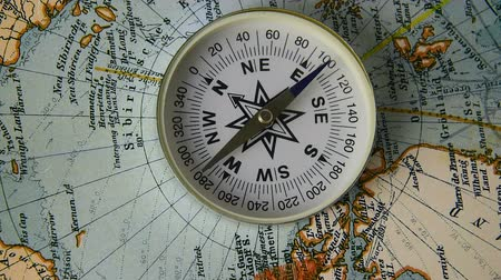 направление : The compass arrow rotates on the geographical map of the world