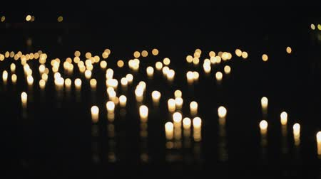 comemoração : Burning candles float on water during Loi Khrathong celebration in Sukhothai, Thailand. In and out of focus. Vídeos