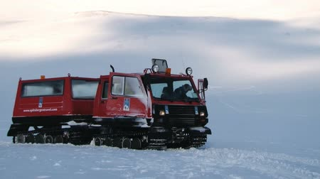 snowcat : Longyearbyen, Norway, March 19, 2014 - People drive red snowcat vehicle on the arctic snow in the mountains of Spitsbergen (Svalbard) archipelago near the town of Longyearbyen, Norway. Distance from Longyearbyen to the North pole is 1316 km, and snowcat i