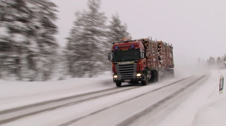 finlandês : Saariselka, Finland - February 18, 2013: Heavy truck transporting timber passes by the winter road covered with ice and snow in Saariselka, Finland.