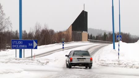 saariselka : Ivalo, Finland - February 16, 2013: Car passes crossroad by the ice road in the arctic town of Ivalo, Finland.