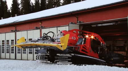 snowcat : Trysil, Norway, March 25, 2014 - Driver takes red snowcat machine out of the garage to prepare ski slopes in Trysil, Norway.