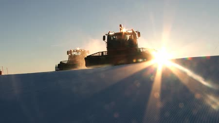 snowcat : Trysil, Norway, March 25, 2014 - People drive snowcat machines preparing ski slopes at sunset in Trysil, Norway. Stock Footage
