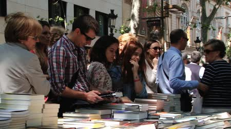 книжный магазин : Barcelona, ??Spain, April 23, 2014 - People buy books at the street market in Barcelona, ???? Spain. Стоковые видеозаписи