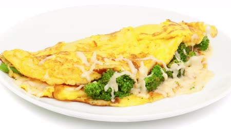 Omelet with cheese and broccoli on a white plate 影像素材