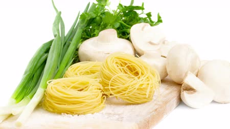 Raw pasta nests and ingredients for mushroom sauce motion slow