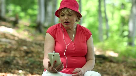 hat : Senior woman in red hat sits on a fallen tree in forest and communicates via smartphone