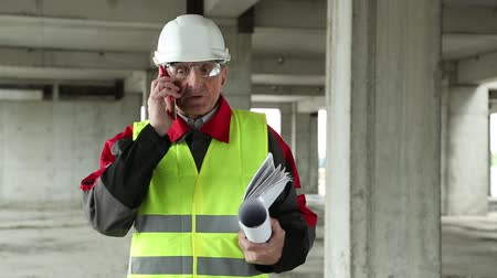 гражданский : Builder in green vest talks on telephone on project site. He holds rolls and sheet of paper with plan Стоковые видеозаписи