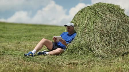 hay cock : Man in dark blue t-shirt with tablet PC sits near a haystack Stock Footage