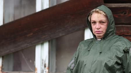 unlucky : Senior woman in green raincoat stands near the boarded-up uninhabited house and looking at the camera Stock Footage