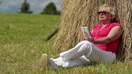 hay cock : Blonde woman with white smartphone sits near haystack and listening to music. Senior woman in red t-shirt with white smartphone listening to music