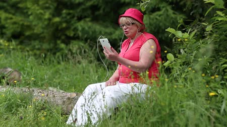 üdvözlettel : Woman in red cap sits on a fallen tree in the forest and communicates via smartphone