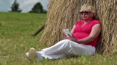 hay cock : Senior blonde woman sits on a green grass near haystack and uses smartphone. Woman with mobile phone Stock Footage
