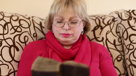 bookshop : Senior woman sits on a divan and reads old book