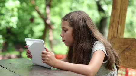 spite : Beautiful girl with tablet computer sits on the bench in summerhouse. Angry girl with Tablet-PC sits on the bench in bower. True sincere emotions. Girl playing the game on his tablet computer