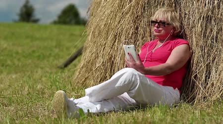 hay cock : Senior woman in red t-shirt with white smartphone listening to music. Blonde woman with white smartphone sitting near haystack and listening to music