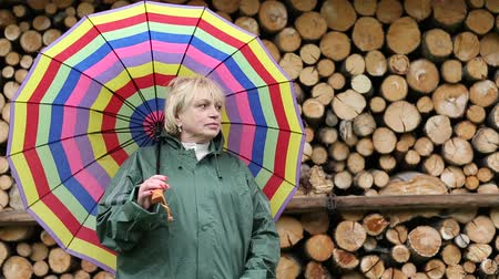 пиломатериалы : Blonde woman in green slicker with big multicoloured umbrella stands near lumber