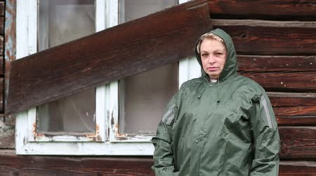 spite : Woman in waterproof raincoat stands near the boarded-up uninhabited house and looks at the camera Stock Footage