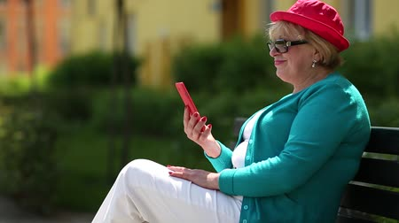 hat : Senior woman in red hat sits on the bench and communicates via smartphone