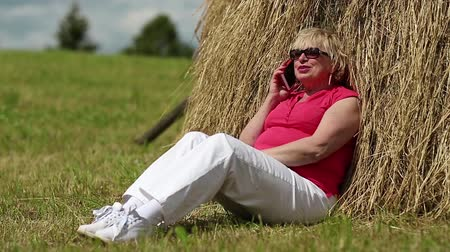 hay cock : Senior woman sits near haystack and communicates via mobile phone. Blonde woman with smartphone Stock Footage