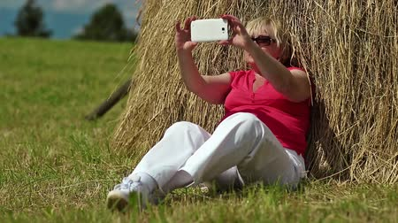 hay cock : Pretty blond woman sits on green grass near haystack and makes photos on his smartphone