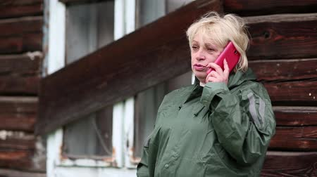preciso : Woman in green raincoat stands near uninhabited house and  talks on cell phone. Blond woman stands near derelict hut and communicates via red smartphone. She holds smartphone in left hand