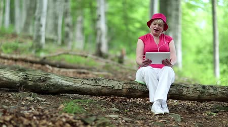 hat : Senior woman in red hat sits on a fallen tree in deciduous forest and communicates via tablet PC
