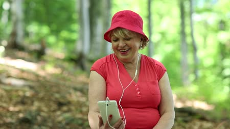 hat : Senior woman in red hat sits on a fallen tree in the forest and communicates via smartphone. Woman with smartphone communicates network