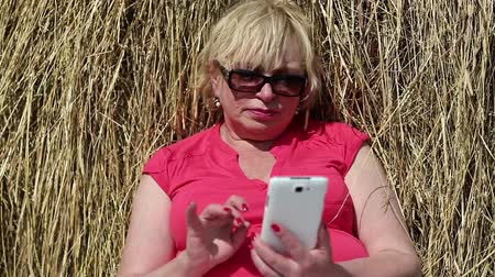 hay cock : Senior blonde woman sits near haystack and uses smartphone. Woman with mobile phone Stock Footage