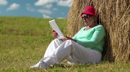 hay cock : Senior blonde woman sits on a green grass near haystack and uses Tablet PC. Woman with tablet computer