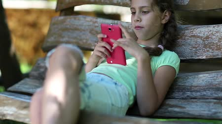 клетка : Beautiful girl with red smartphone sits on the swing bench. Little girl with cell phone sits on the bench in garden. Girl communicates via mobile phone. Pretty girl uses his smartphone