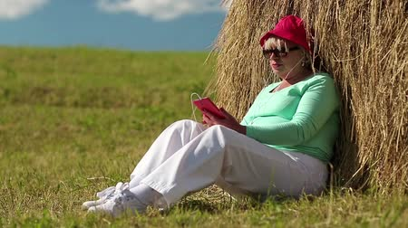 hay cock : Blonde woman with red smartphone sits near haystack and listens to music. Senior woman in green t-shirt with red smartphone sits on the grass and listens to music