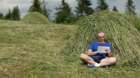 hay cock : Man in dark blue t-shirt with tablet computer sits near a hayrick Stock Footage