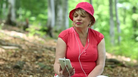 eyes closed : Woman in red t-shirt and red cap in the forest listens to music on his smartphone. Blonde woman in red cap sits on a fallen tree in the forest and listens to music. Female with smartphone in the wood