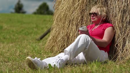 hay cock : Blonde woman with white smartphone sits near haystack and listens to music. Senior woman in red t-shirt with white smartphone listening to music Stock Footage