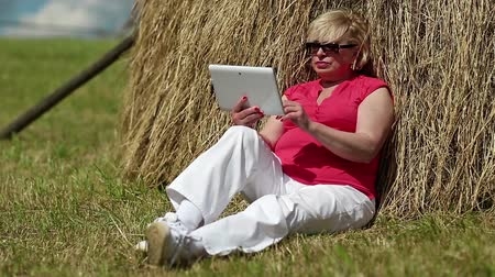 hay cock : Blonde woman sits on a green grass near haystack and uses tablet computer. Woman with tablet computer. Senior womn with white computer