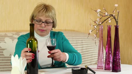 çakmak : Woman pours and drinks red wine. Senior woman sits at a table and drinks red wine. Female drinking wine