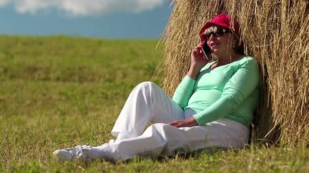 hay cock : Senior woman sits near haystack and communicates via mobile phone. Blonde woman with smartphone. Female in red cap with smartphone. Business woman talks on a mobile phone Stock Footage