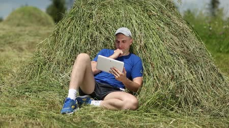 hay cock : Man in dark blue t-shirt with tablet computer lies on a haystack. Man uses tablet PC. Male with tablet computer. Sportsman with Tablet PC