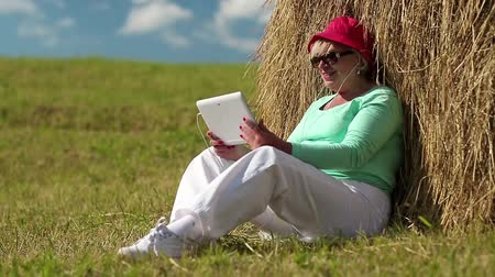 hay cock : Senior blonde woman sits on a green grass near haystack and communicates via tablet computer. Female with tablet computer. Businesswoman with Tablet PC communicates through Skype